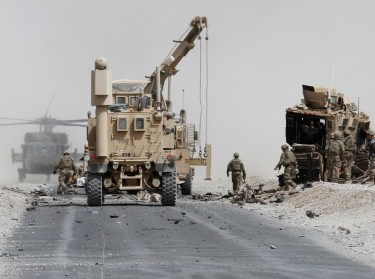 U.S. troops assess the damage to an armored vehicle of the NATO-led military coalition after a suicide attack in Kandahar province, Afghanistan, August 2, 2017