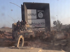 An Iraqi military HMMWV drives past an Islamic State sign in eastern Mosul after they captured it from IS