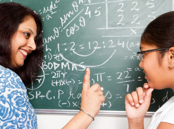 A teacher discussing a mathematics problem with her student