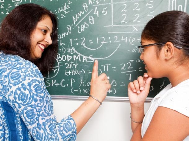 A teacher discussing a mathematics problem with her student