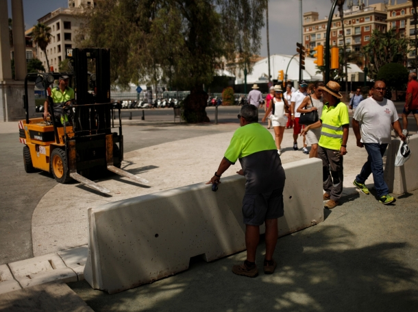 Workers place concrete barriers to prevent possible attacks on the walk Muelle Uno in Malaga, Spain, on August 18, 2017, a day after a van crashed into pedestrians at Las Ramblas