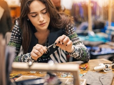 A young woman holding pliers as she makes jewelry