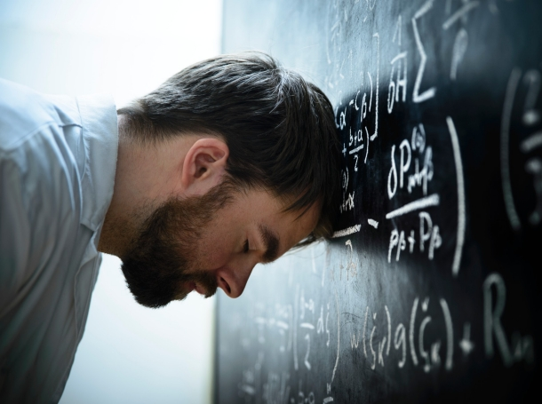 Stressed researcher with head on blackboard filled with formulas and equations