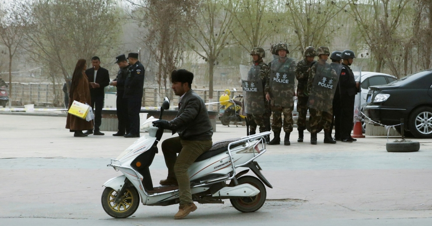 Police officers check the identity cards of a people as security forces keep watch in Kashgar, Xinjiang Uighur Autonomous Region, China, March 24, 2017
