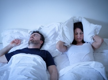 Woman covering her ears with her pillow as her partner snores