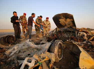 Iraqi security forces inspect the site of a bomb attack at a police checkpoint on a highway near the southern Iraqi city of Nassiriya, Iraq, September 14, 2017
