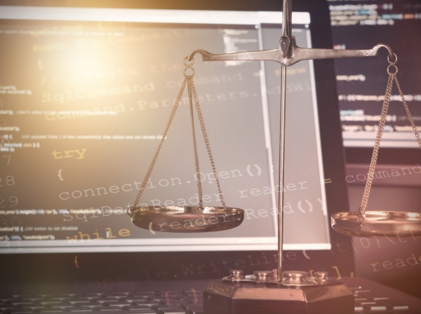 Scales of justice in front of computer monitors with code
