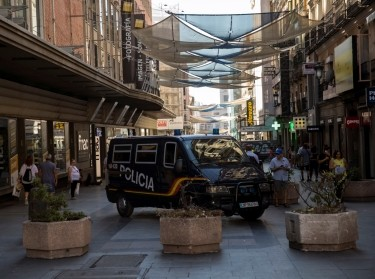 A police van parks near pots placed to prevent possible attacks on a pedestrian street in Madrid, Spain, August 18, 2017