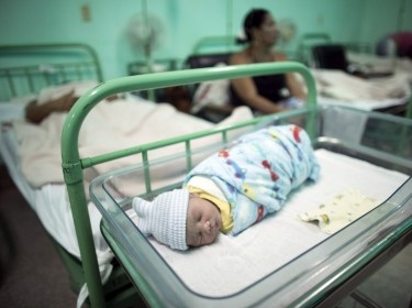 A newborn baby rests beside his mother at the Ana Betancourt de Mora Hospital in Camaguey, Cuba, June 19, 2015, the week the World Health Organization declared Cuba the first country in the world to eliminate the transmission of HIV and syphilis from mother to child