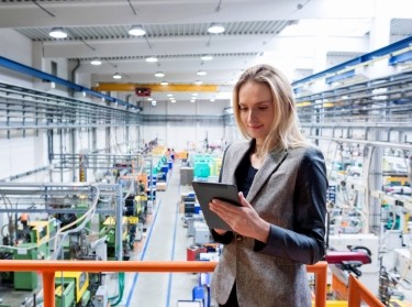 A woman inspects a manufacturing plant