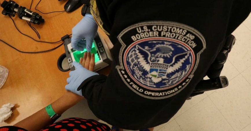 A woman seeking asylum has her fingerprints taken by a U.S. Customs and Border patrol officer at a pedestrian port of entry from Mexico to the United States, in McAllen, Texas, U.S., May 10, 2017