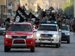 Militant Islamist fighters waving flags, travel in vehicles as they take part in a military parade along the streets of Syria's northern Raqqa province June 30, 2014