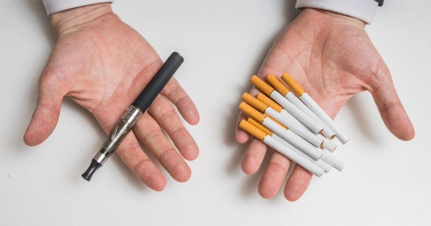 Hands holding electronic and conventional tobacco cigarettes