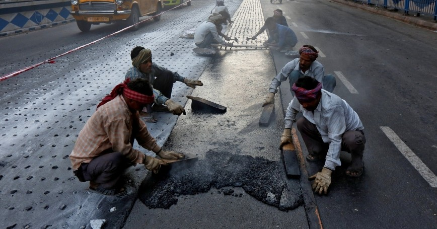 Laborers work at a road construction site in Kolkata, India, February 27, 2017