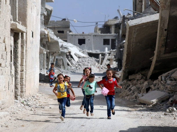 Children run along a damaged street as they celebrate the first day of the Muslim holiday of Eid al-Adha at a rebel-held area in Deraa, Syria, September 1, 2017
