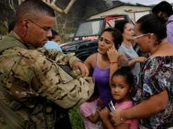 SFC Eladio Tirado, who is from Puerto Rico, speaks with residents as he helps during recovery efforts following Hurricane Maria, in San Lorenzo, Puerto Rico, October 7, 2017