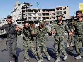 Fighters of Syrian Democratic Forces dance after liberating Raqqa from Islamic State militants, Raqqa, Syria, October 18, 2017
