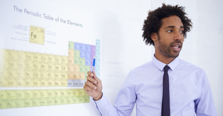 A male science teacher explaining the periodic table