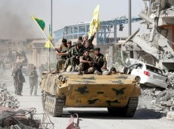 Syrian Democratic Forces fighters ride atop of military vehicle as they celebrate victory in Raqqa, Syria, October 17, 2017