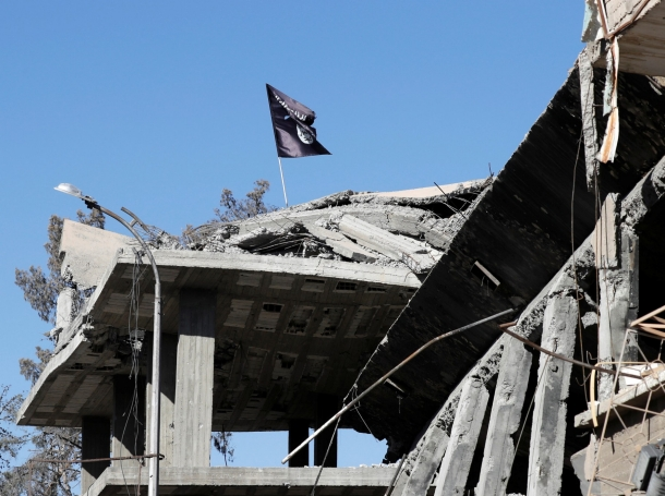 A flag of Islamic State militants is pictured above a destroyed house near the Clock Square in Raqqa, Syria, October 18, 2017