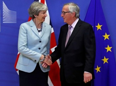 Britain's Prime Minister Theresa May is welcomed by European Commission President Jean-Claude Juncker at the EC headquarters in Brussels, Belgium, December 8, 2017