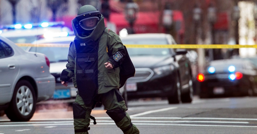 A law enforcement bomb technician walks away after preparing the controlled detonation of a suspicious object during a search for a suspect in the Boston Marathon bombing, in Watertown, Massachusetts, April 19, 2013