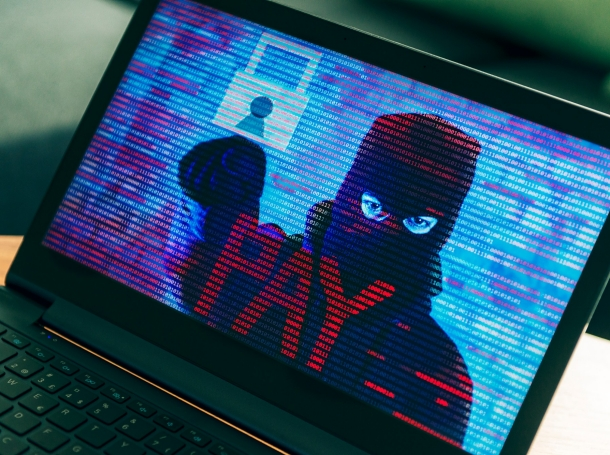 Criminal hiding behind a mask on computer screen asking the owner for money