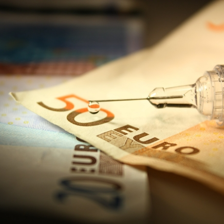 A syringe over Euro notes