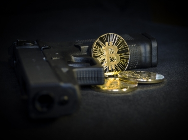 Shiny gold Bitcoin coin with gun on black background
