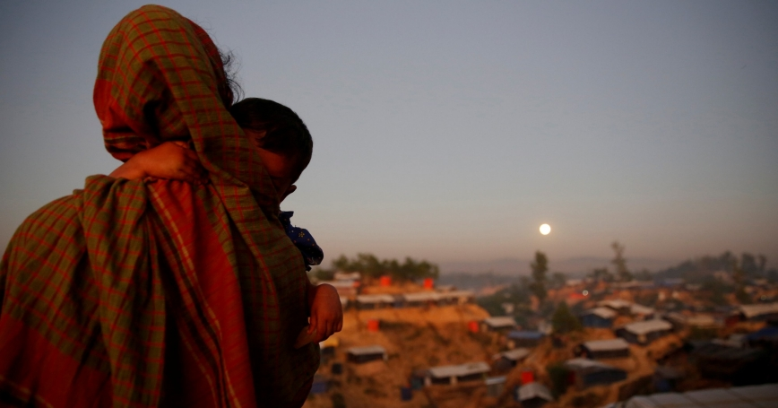 A Rohingya refugee looks at the moon with a child in tow at Balukhali refugee camp, Bangladesh, December 3, 2017