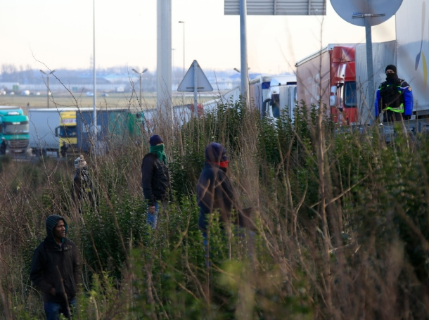 A French gendarme stands guard near a line of lorries as migrants wait in bushes in the hopes of boarding a truck to make their way across the Channel to Britain, near Calais, France, Janaury 21, 2016