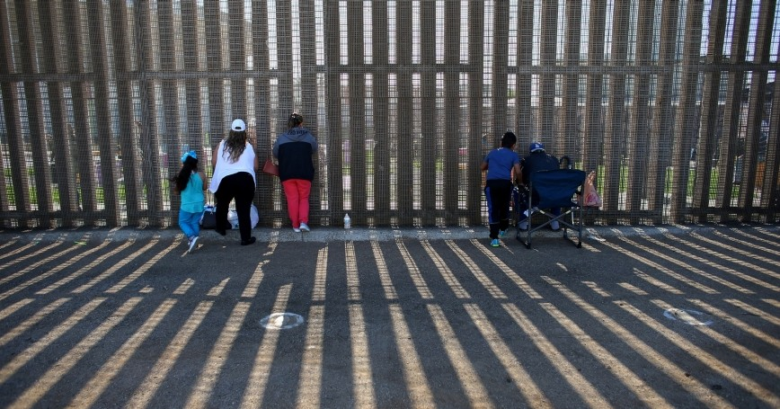 People speak through the U.S.-Mexico border wall at Border Field State Park in San Diego, California, November 18, 2017