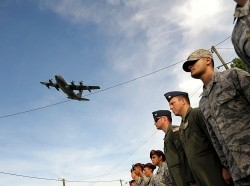 A C-130J Super Hercules aircraft flies over a formation of Airmen during a ceremony to remember veterans of World War II on the 70th anniversary of D-Day in Picauville, France, June 6, 2014