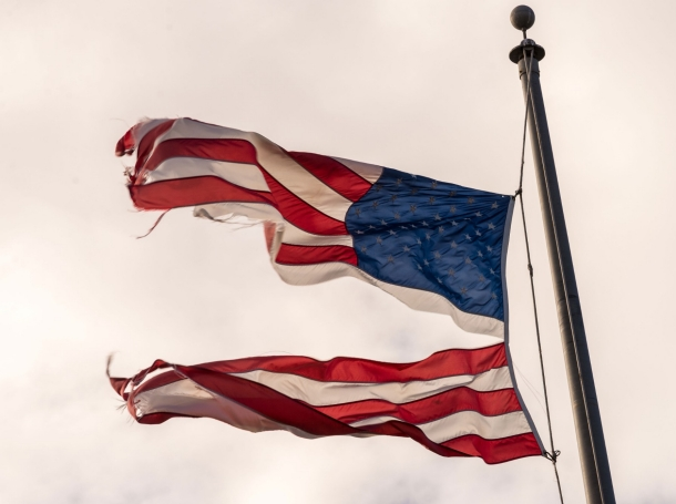 Torn American flag waving in the wind on a cloudy day