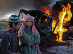 Two boys stand near fuel trucks that were set ablaze in the Bolan district of Pakistan's Baluchistan province, December 12, 2011