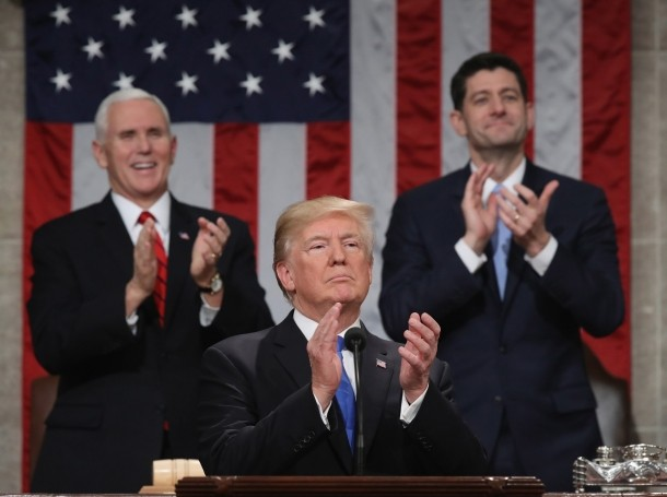 U.S. President Donald Trump applauds in front of Vice President Mike Pence and Speaker Paul Ryan during his first State of the Union address in Washington, January 30, 2018
