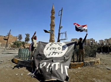 Shi'ite Popular Mobilization Forces (PMF) members hold an Islamic State flag, which they pulled down, during the war between Iraqi army and PMF against Islamic State militants in Tal Afar, Iraq, August 27, 2017
