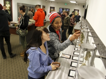 Young adults browse samples at Shango Cannabis on the first day of legal recreational marijuana sales in Portland, Oregon, October 1, 2015