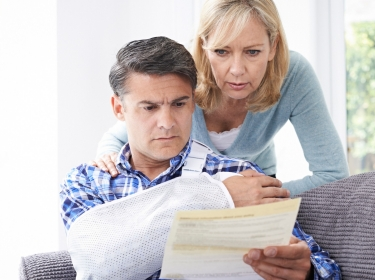An injured man and his wife examine a bill