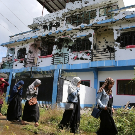 Residents who returned from evacuation centers walk past a bullet-ridden house believed to have been rented by pro-Islamic State militant group leaders before their attack on the region, in Basak Malutlut district in Marawi City, Philippines, October 29, 2017