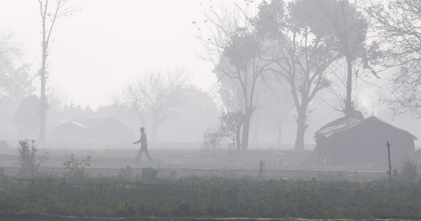 A man walks through a field amidst smog in New Delhi, India, February 7, 2018.