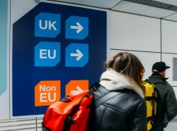 Passengers walks past sign prior to immigration control