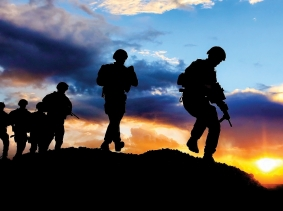 Silhouetted soldiers on patrol at sunset