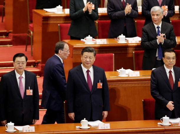 Wang Qishan walks past Zhang Dejiang, Chinese President Xi Jinping, and Chinese Premier Li Keqiang at the opening session of the National People's Congress in Beijing, China, March 5, 2018