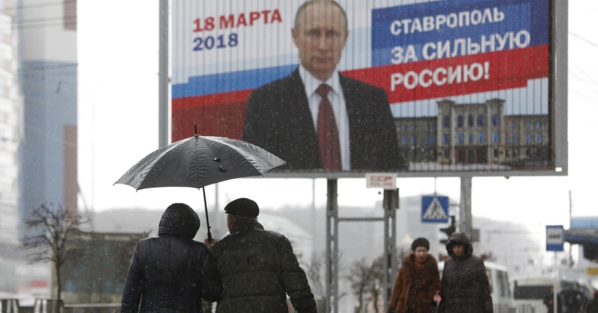 People walk next to an election campaign poster of Russian President Vladimir Putin in Stavropol, Russia, March 14, 2018
