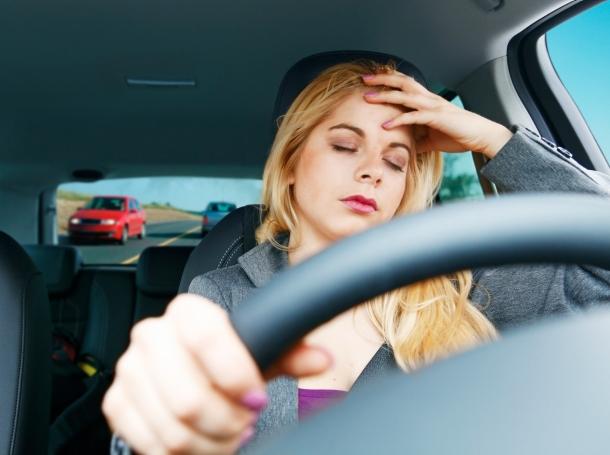 A tired teen girl driving a car