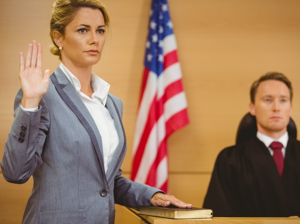 A witness in a courtroom swearing to tell the truth