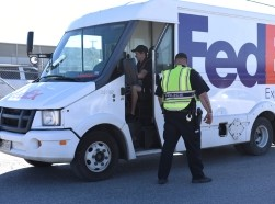 An officer with Schertz Police Department holds a FedEx truck from entering the scene of a blast at a FedEx facility in Schertz, Texas, U.S., March 20, 2018