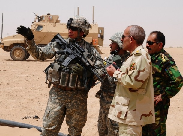 A U.S. Military Transition Team leader speaks with his Iraqi counterpart during a mission to find weapons caches in the western desert near Bayji, Iraq