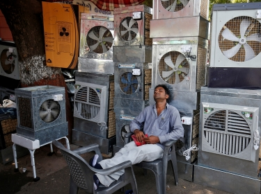 A man selling air coolers rests at a market on a hot summer day in Ahmedabad, India May 4, 2017